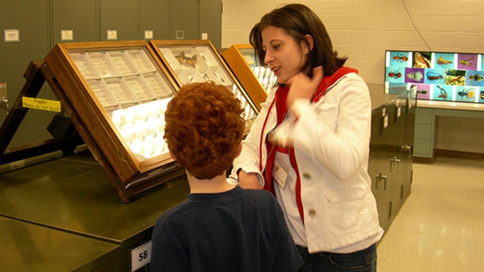 Volunteer Anne Nichols in the Triplehorn collection with a young visitor